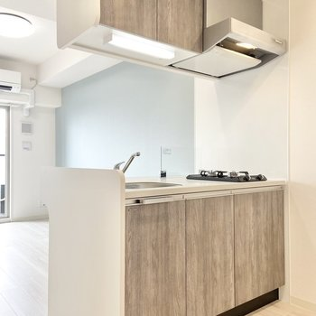 【LDK】キッチンは対面式で、優しいカラーリング。(※写真は15階の同間取り別部屋のものです)