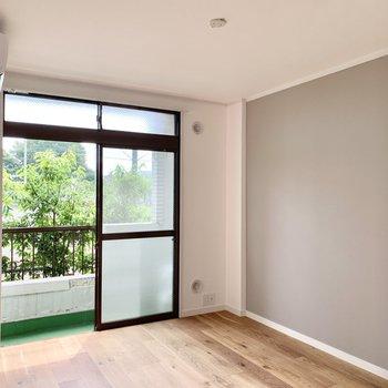 【洋室】窓からの緑と、グレーのアクセントクロスが優しく包んでくれます。