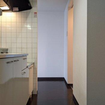 【LDK】キッチンは1人が通れる幅です。奥は脱衣所に行くことができます。