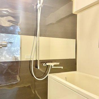 バスルームには大きな横長の鏡。シャワーヘッドがメタリックなのも◎