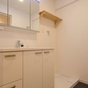 脱衣所も広々!洗濯機置場の上には洗剤などを置ける木製の棚を設置。※写真は反転間取り別部屋のもの