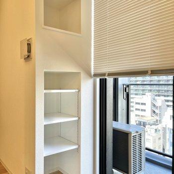 窓にはブラインド、そばにはちょっとした棚もあります。