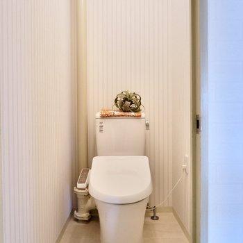 温水洗浄機付きのお手洗い。ストライプのクロスが可愛らしいですね。