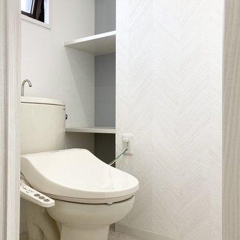 玄関挟んで隣にはトイレ。ペーパーストックや掃除道具置きに便利な大きな棚付き。(※写真はクリーニング前のものです)