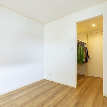 ダブルベッドと壁付けでシェルフを置こう。奥にはオープンクローゼット。