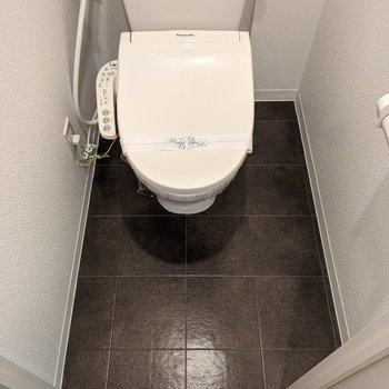 タイル張り、温水便座機能付きのトイレです。