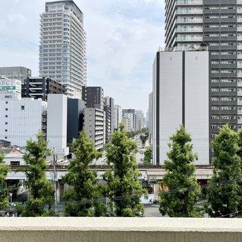 近景に街路樹、中景と遠景に高層ビルという、都会らしい眺め。またすぐそばには線路もあります。