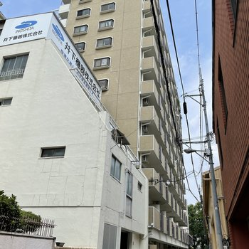 大通りのすぐそばにあるマンション。入り口は路地に面しています。