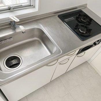 システムキッチンは2口コンロ、グリルつき。(※写真は7階の同間取り別部屋のものです)