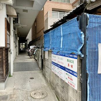 マンション入り口の通路にゴミ置き場と駐輪場。