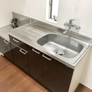 キッチンはダークブラウン。シンクも広く作業スペースもしっかり!(※写真は同間取り別部屋、清掃前のものです)