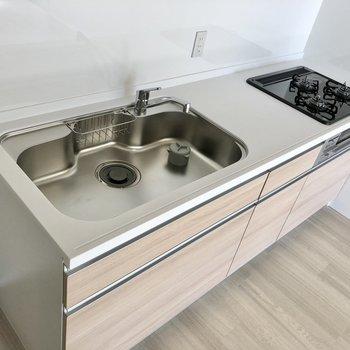 システムキッチンは3口コンロにグリル付き。シンクも広々!(※写真は2階の同間取り別部屋のものです)