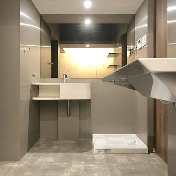 ワイドな鏡に洗面台、洗濯機置場。右奥の扉の中に…?(※写真は4階の同間取り別部屋のものです)