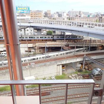 【共用部】廊下の階段からは、高架をくぐる電車たちが。