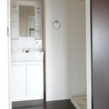 脱衣所には洗面台と洗濯機置場。(※写真は6階の同間取り別部屋のものです)
