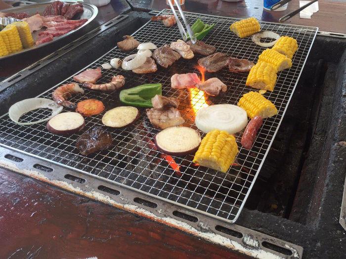 バーベキューで野菜や肉を焼いている様子