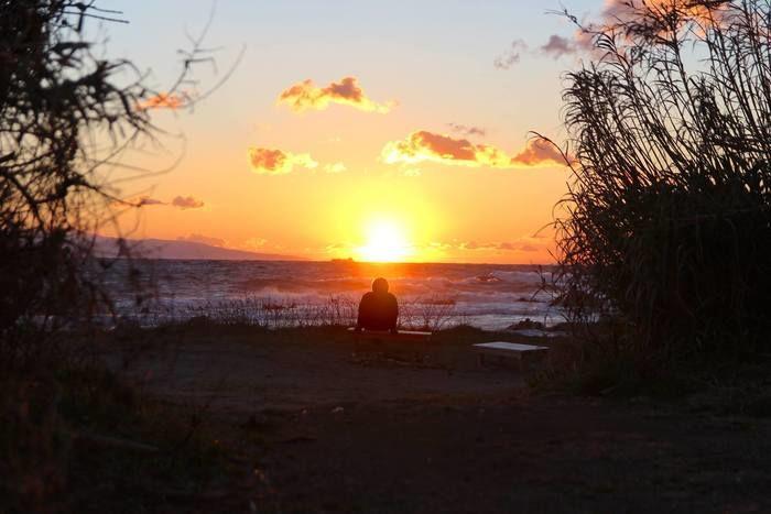 海越しに夕日を見ている人