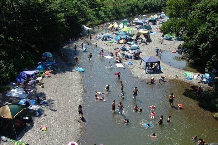川沿いにテントを貼って、川で遊んでいる人たち