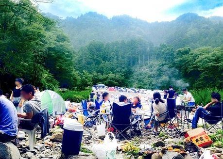 河原でバーベQを楽しむ人々