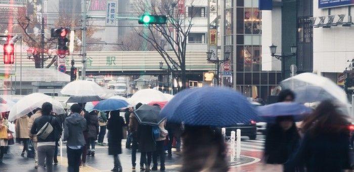 雨の日の渋谷駅前と傘をさして歩く人々