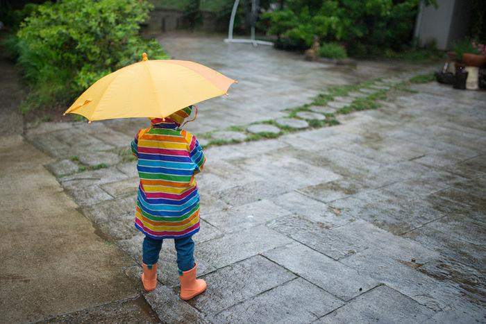 カッパを着て傘を持っている子供の写真