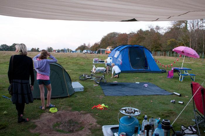 広いテントサイトでキャンプをしている女性の写真