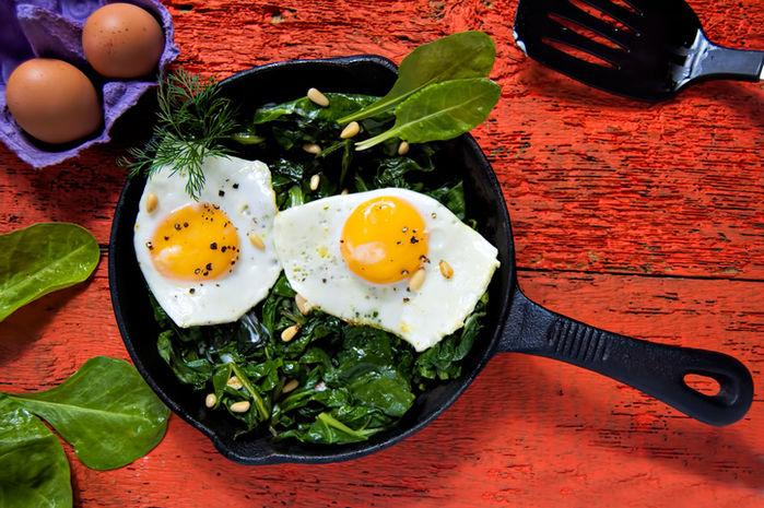 スキレットで目玉焼きと小松菜を調理している写真