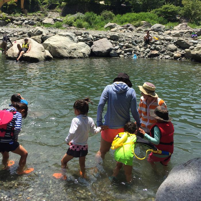 川で遊んでいる家族の写真