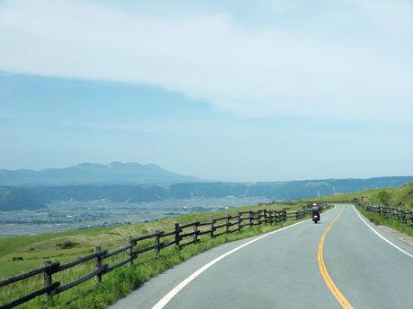 自然に囲まれた道路をバイクで走っている写真