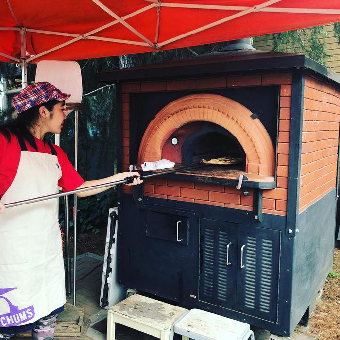 釜でピザを焼いている男性の写真