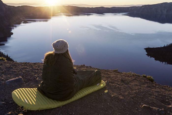 湖の辺りでマットレスに座っている女性の写真