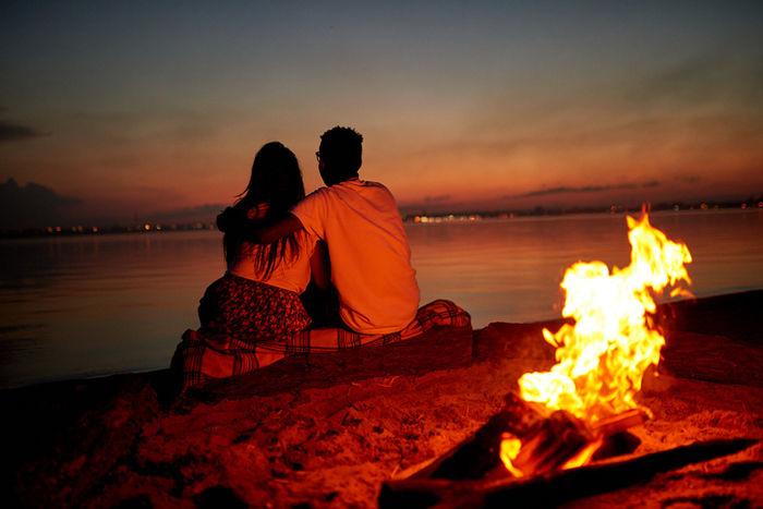 焚き火を焚きながら、海沿いで2人で座っているカップルの写真