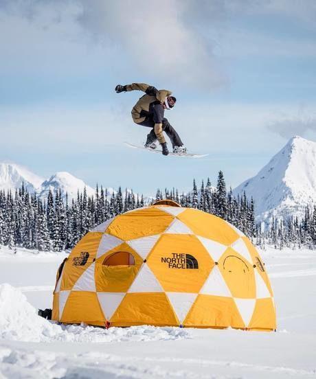 スノボでテントの上をジャンプしている写真