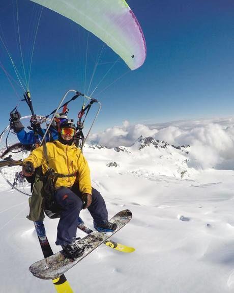 スノボの格好をしながらパラシュートをしている人の写真