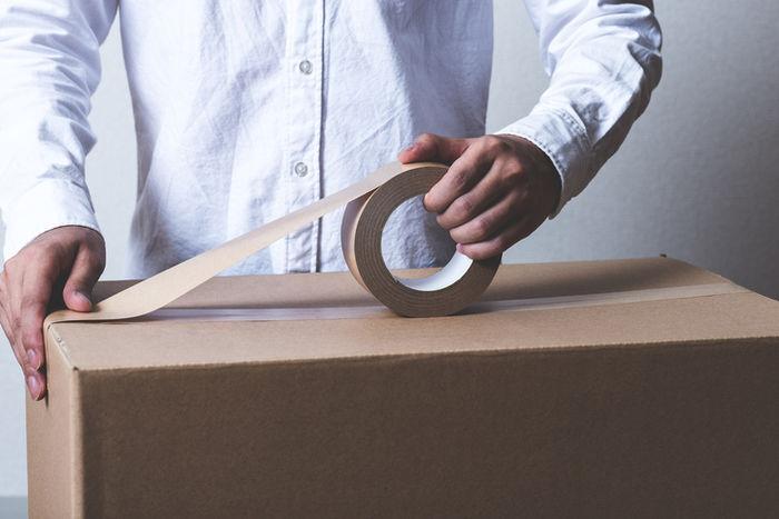ダンボールにガムテープを張っている人の写真