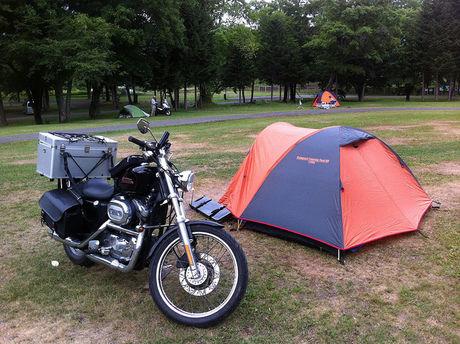 キャンプ場のバイクとテントの写真