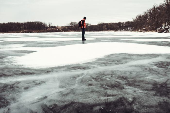 凍った湖に立っている男性の写真