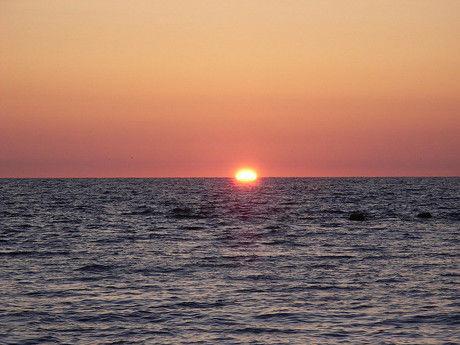 水平線に沈む夕日の写真
