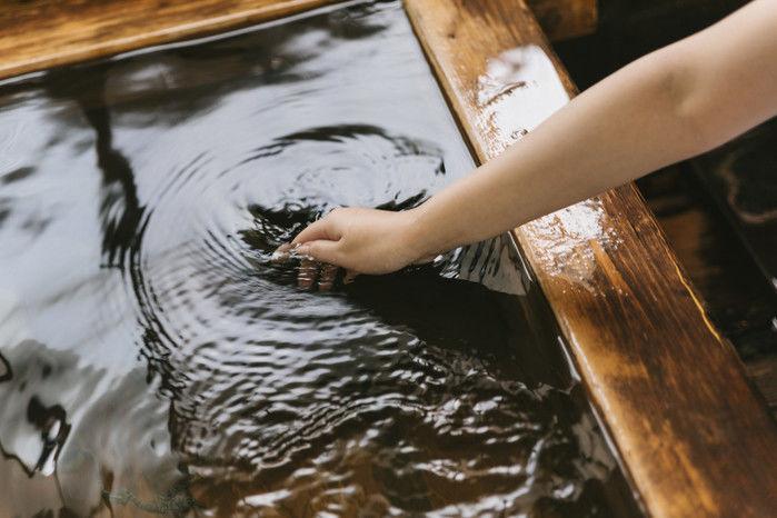 温泉に手をつけている人の写真