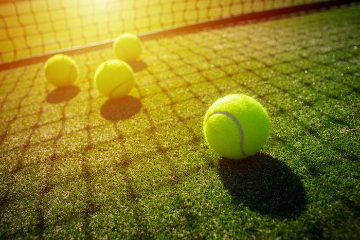 テニスコートに転がっているテニスボールの写真