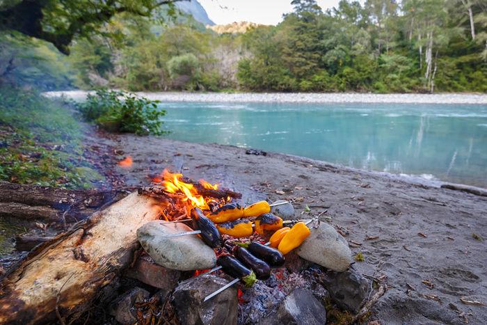 綺麗な川の近くで焚き火をしている写真