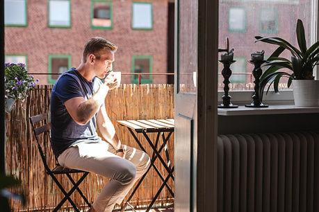 バルコニーでコーヒーを飲む男性の写真