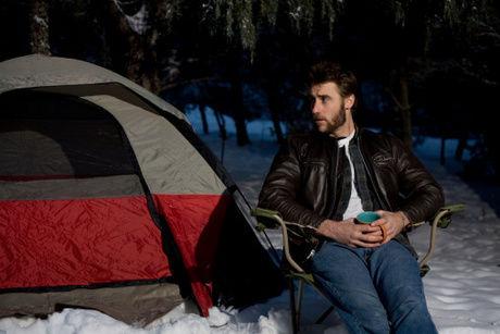レザージャケットを来て冬キャンプをしている男性の写真