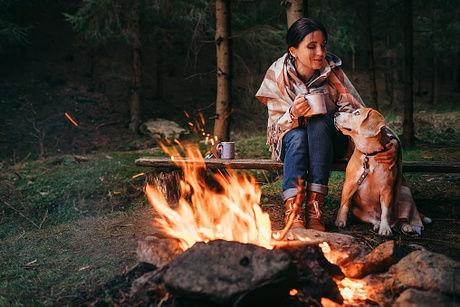 焚き火をして犬と温まっている女性の写真