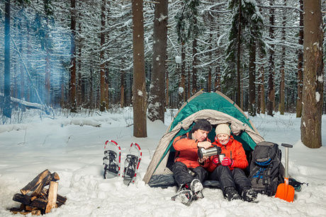 雪上にテントを貼って冬キャンプをしている夫婦の写真