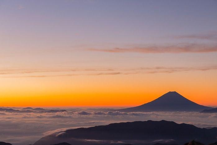 朝焼けに照らされた富士山の写真