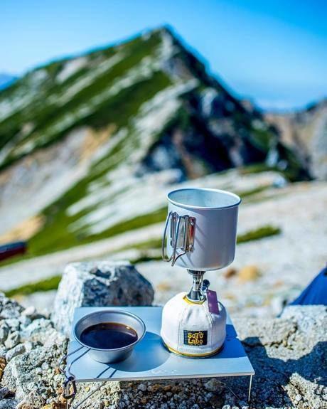 石の上に置いてあるシェラカップをガス缶の写真