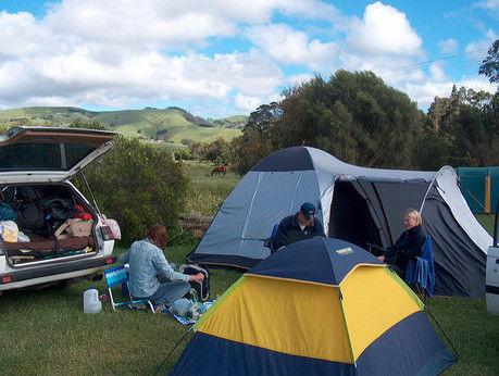 デイキャンプサイトでテントを貼ってくつろいでいる人たち