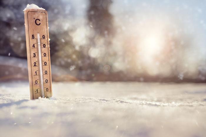 雪の地面に刺さっている温度計