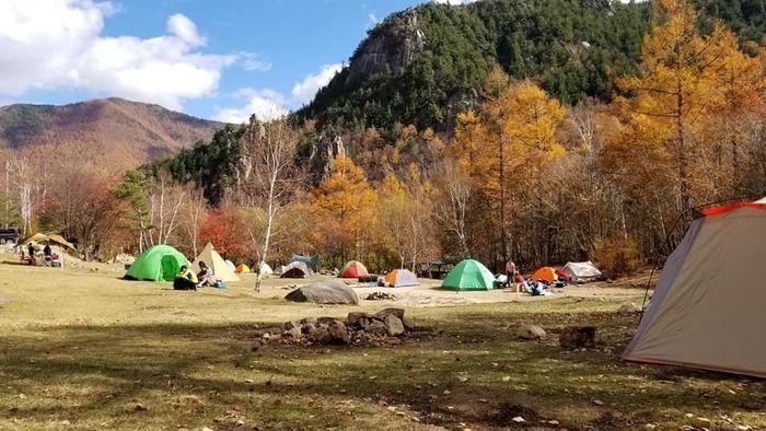 山の麓のテントサイトでテントがたくさん張ってある写真